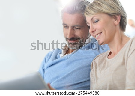 Middle-aged couple websurfing on internet with touchpad - stock photo