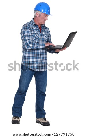 middle aged craftsman standing with laptop - stock photo