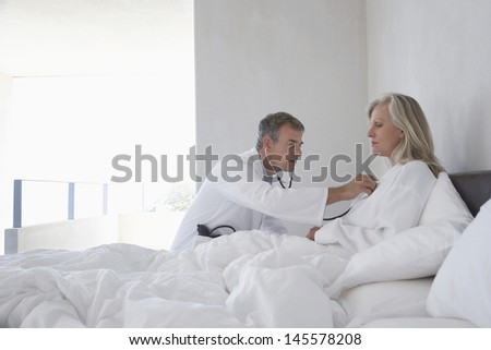 Middle aged doctor examining woman with stethoscope in bed at home - stock photo