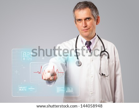 Middle aged doctor standing and pressing modern medical type of button - stock photo