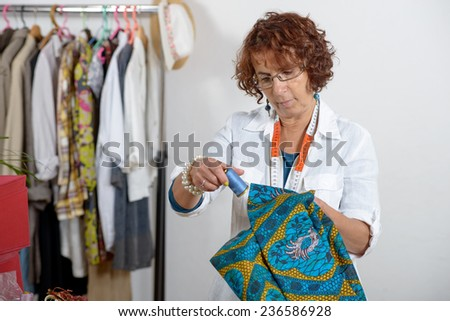 middle-aged dressmaker working in his workshop - stock photo