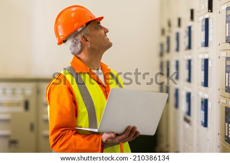 middle aged electrical engineer with laptop computer in control room - stock photo