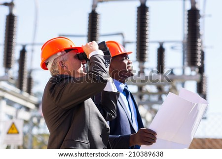 middle aged engineer and colleague with binoculars on electrical substation - stock photo