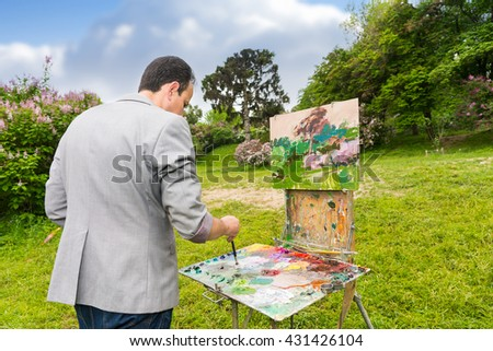 Middle-aged fashionable male painter mixing colors of oils and acrylics paint with a paintbrush on a palette in a park  during an art class - stock photo
