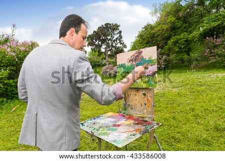 Middle-aged fashionable male professional artist finishing his work of a garden scene with flowers on a sketchbook  outdoors - stock photo