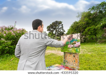 Middle-aged fashionable male professional artist working on a sketchbook painting a garden scene with flowers outdoors - stock photo