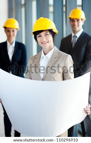 middle aged female architect holding blue print in front of colleagues - stock photo