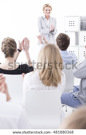 Middle-aged female manager looking happily at a group of employees clapping hands at her