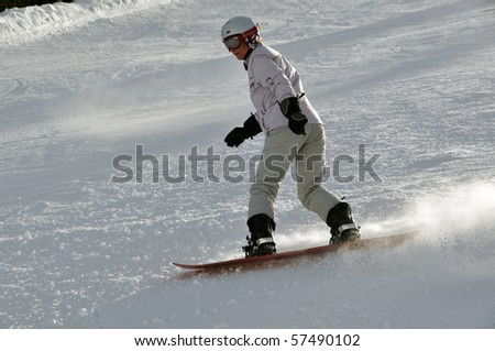 Middle aged female snowboarder wearing helmet and snow goggles in powder snow on steep hill - shot in Livigno, Italian Alps