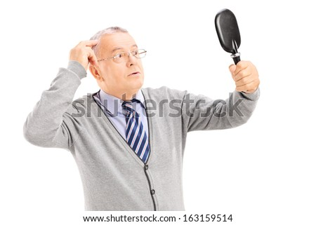 Middle aged gentleman checking for thinning hair in the mirror isolated on white background - stock photo