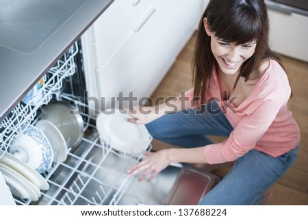 middle aged girl in the kitchen using dishwasher.  view of young woman in kitchen doing housework - stock photo