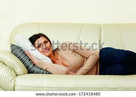 Middle-aged happy woman lying on the sofa at home