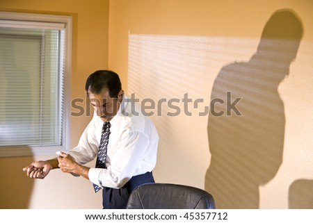 Middle-aged Hispanic businessman rolling up sleeve looking down reading in boardroom - stock photo