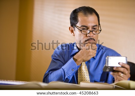 Middle-aged Hispanic businessman working in office holding mobile phone reading text message - stock photo