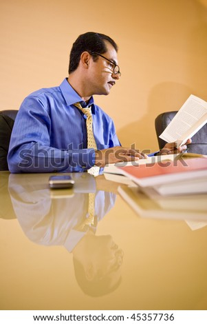 Middle-aged Hispanic businessman working in office reading reference book - stock photo