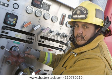 Middle aged hispanic firefighter holding hose - stock photo
