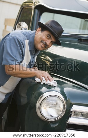 Middle-aged Hispanic man waxing classic car - stock photo