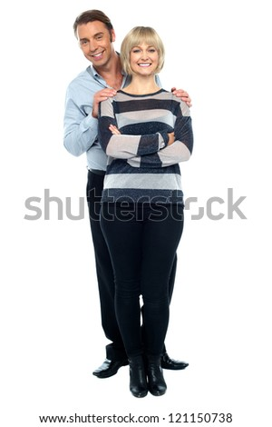 Middle aged husband holding his wife from behind. Wife posing smartly with crossed arms. - stock photo
