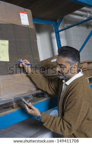 Middle aged Indian man making inventory in factory - stock photo