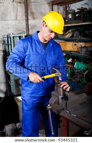 middle aged industrial craftman working in workshop