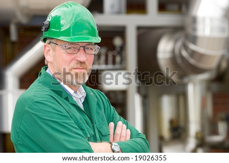 Middle aged industrial worker in front of some tubes - stock photo