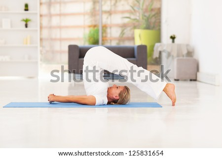 middle aged lady doing yoga at home - stock photo