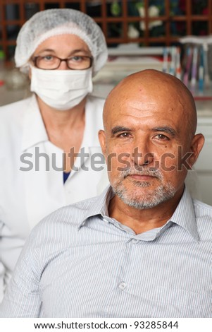 Middle aged latin man with the dentist in the background - stock photo