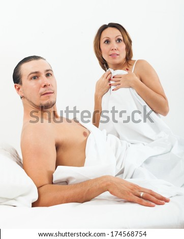 Middle-aged loving couple caught during adultery in bed - stock photo