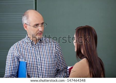 Middle-aged male lecturer and a young female student in a discussion standing close together in front of a blackboard chatting - stock photo