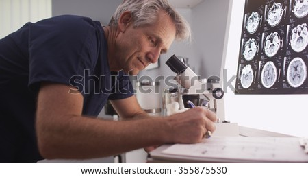 Middle aged male radiologist looking through microscope - stock photo