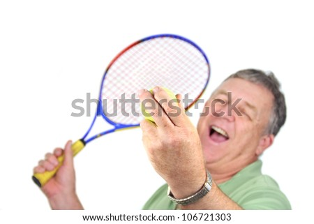 Middle aged man about to serve a tennis ball.
