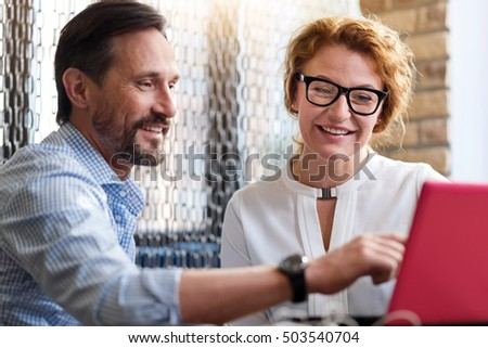 Middle-aged man and woman discussing information from laptop