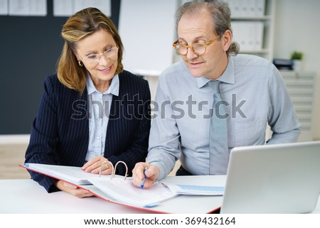 middle-aged man and woman in the office sitting at a desk discussing papers - stock photo