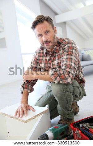 Middle-aged man at home assembling furniture parts