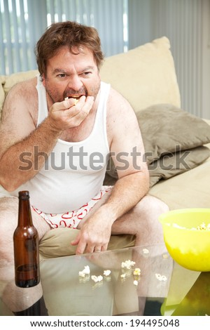 Middle aged man at home on the couch watching tv, drinking beer, and eating popcorn, in his underwear.   - stock photo