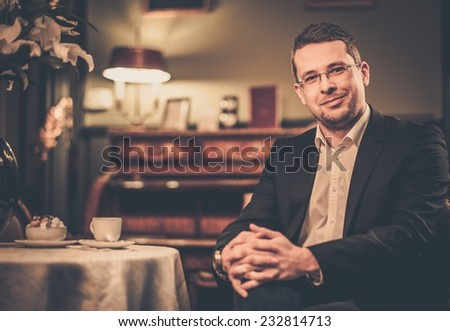 Middle-aged man behind table in luxury vintage style interior