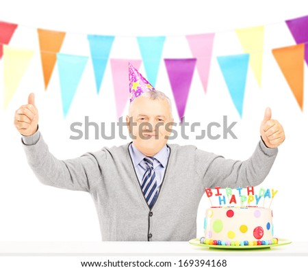 Middle aged man celebrating his birthday giving thumbs up, isolated on white background  - stock photo