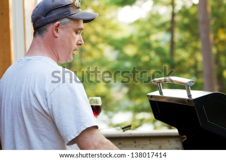 middle aged man cooking on a BBQ - stock photo