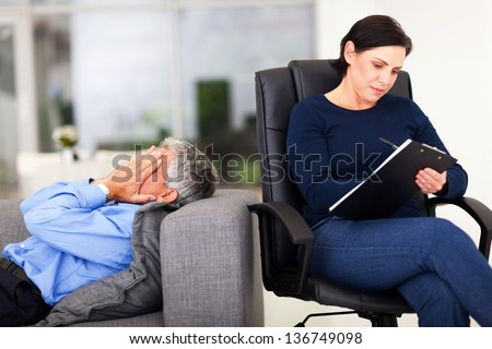 middle aged man crying during session with therapist in office - stock photo