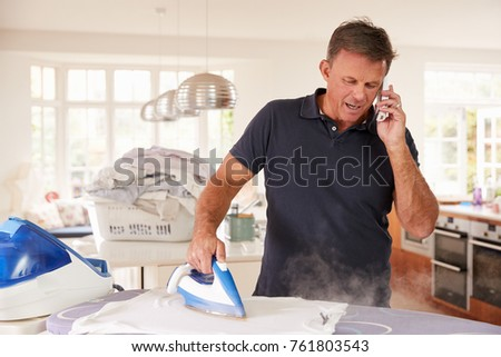 Middle aged man distracted by phone while ironing