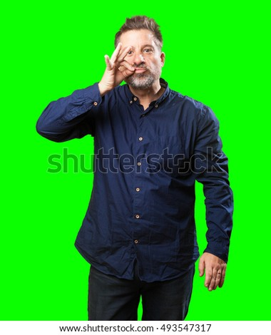 middle aged man doing a silence gesture