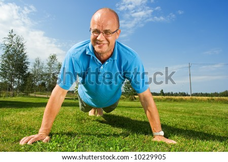 Middle-aged man doing push-ups - stock photo