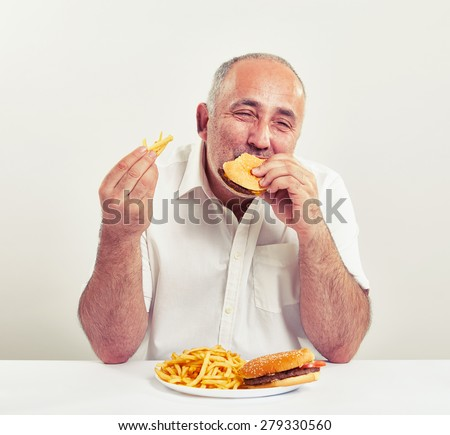 middle-aged man eating burger and french fries with pleased over light grey background