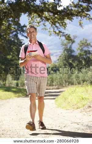 Middle Aged Man Hiking Through Countryside - stock photo
