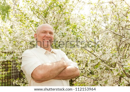 middle-aged man in flowering garden - stock photo