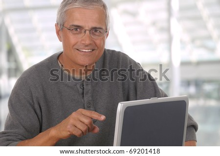 Middle aged man in lobby of modern office building laptop computer. Man is casually dressed and smiling and pointing at the computer. Horizontal composition - stock photo