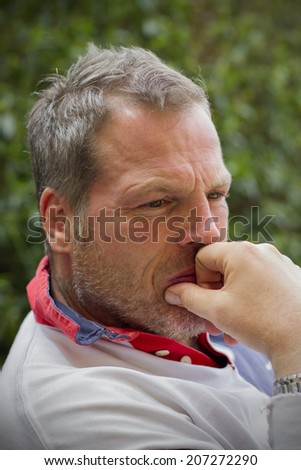 Middle-aged man in thoughtful pose with green leaf background - stock photo