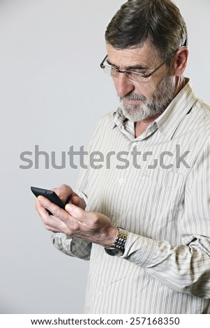 Middle aged man looking at his phone, Studio shot of mature man reading text message on smart phone against grey background - stock photo