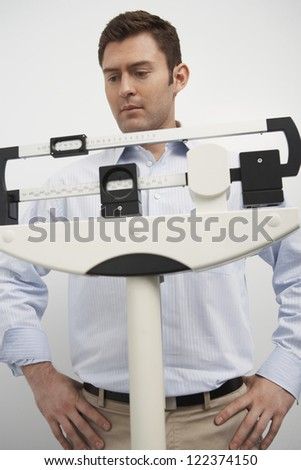 Middle aged man looking at scale of weighing machine - stock photo