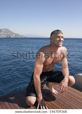 Middle aged man looking away while crouching on yacht's floorboard